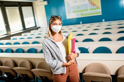 Weiblicher Student, der eine medizinische Gesichtsschutzmaske zum Schutz vor Viren trägt, steht im Hörsaal schulisch schön Kaukasier Hochschule Konzept Korona