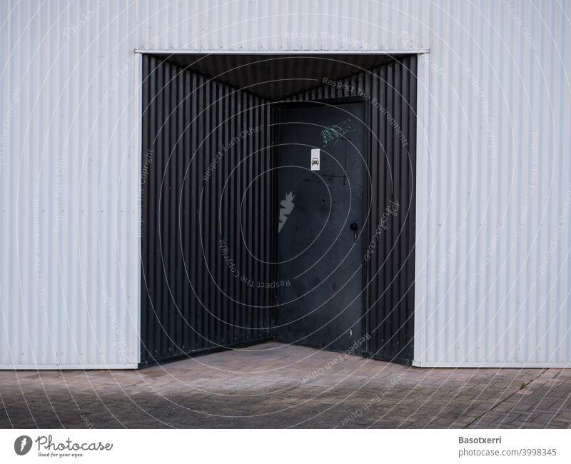Schwarzer Garageneingang an modernem Wohnhaus aus weissem Wellblech Vitoria Baskenland Spanien spanisch Tiefgarage Hochhaus gewellt Wand Fassade Mauer weiß