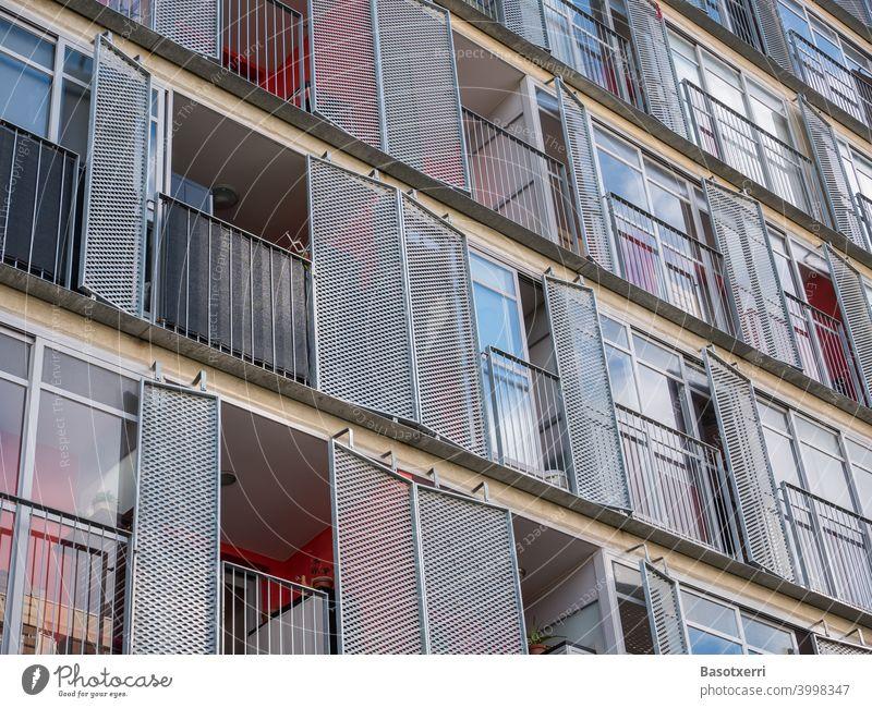 Detailansicht eines modernen Wohnhauses mit Balkons und klappbaren Läden aus Metall Wohnen Hochhaus rot Farbe Glas Laden Fensterladen Himmel Architektur Fassade
