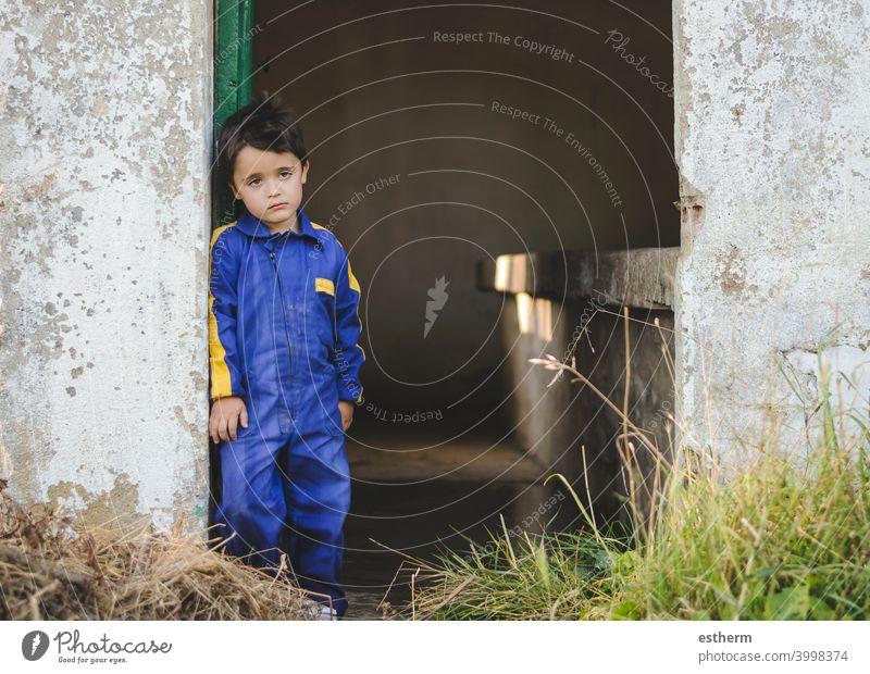 traurig und nachdenklich Kind neben einer Tür Kindheit nostalgisch Gedanke Einsamkeit einsam Ausdruck Freiheit Unschuld unglücklich Porträt ernst träumen