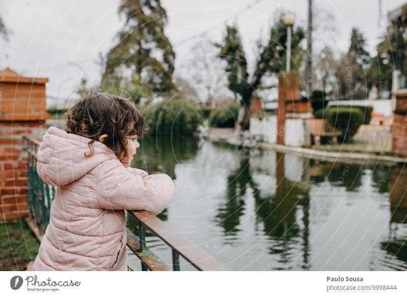 Nettes Mädchen schaut auf den See Kind Kaukasier 1-3 Jahre Park authentisch Natur Mensch Freude Fröhlichkeit Außenaufnahme Tag Kleinkind Lifestyle Kindheit