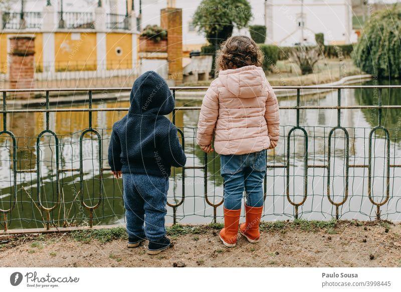 Bruder und Schwester beobachten See Geschwister Brüder Familie & Verwandtschaft Rückansicht unkenntlich authentisch lässig Zusammensein Freundschaft Farbfoto