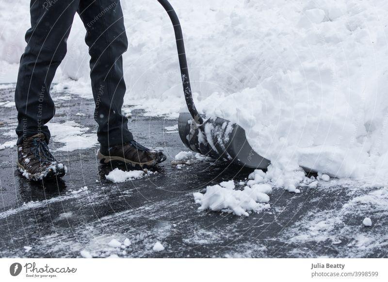 Schnee wird mit einer Schaufel von einer schwarzen Asfalt-Einfahrt geschaufelt; Person in grauer Hose und Stiefeln; großer Schneehaufen Schneesturm schaufeln