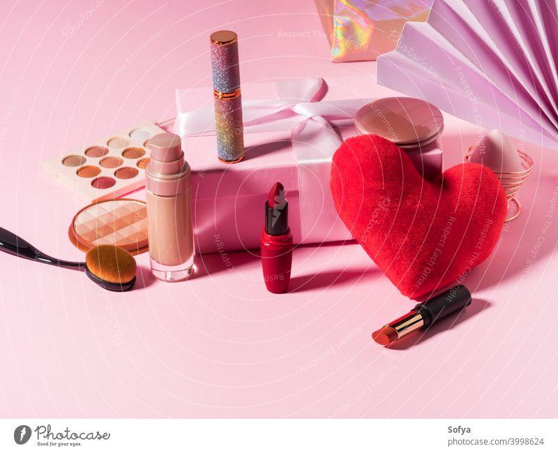 Kosmetik Schönheit Hintergrund mit rotem Herz auf rosa Make-up Produkte Lippenstift Valentinsgruß Fundament zusammenstellen Bürste Anzeige Schatten Mode