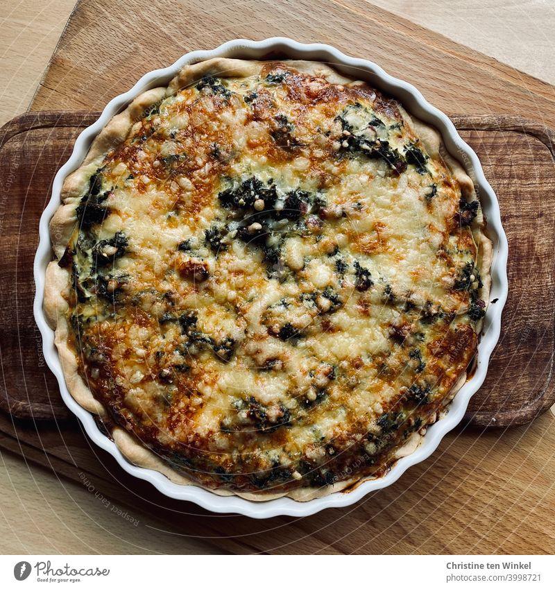 Selbstgebackene leckere Tarte mit Grünkohl und rohem geräuchertem Schinken, mit Käse überbacken. Die Tarteform steht auf Holzbrettchen. Vogelperspektive.
