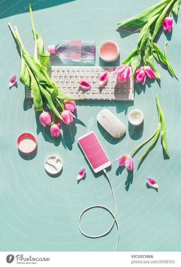 Weibliche Home-Office. Pastell blauen Desktop mit PC-Tastatur, Smartphone mit leeren Bildschirm und Draht, Kosmetika und rosa Tulpen Blumen im Sonnenlicht. Ansicht von oben. Flachlage. Frühlingszeit. Blog-Layout