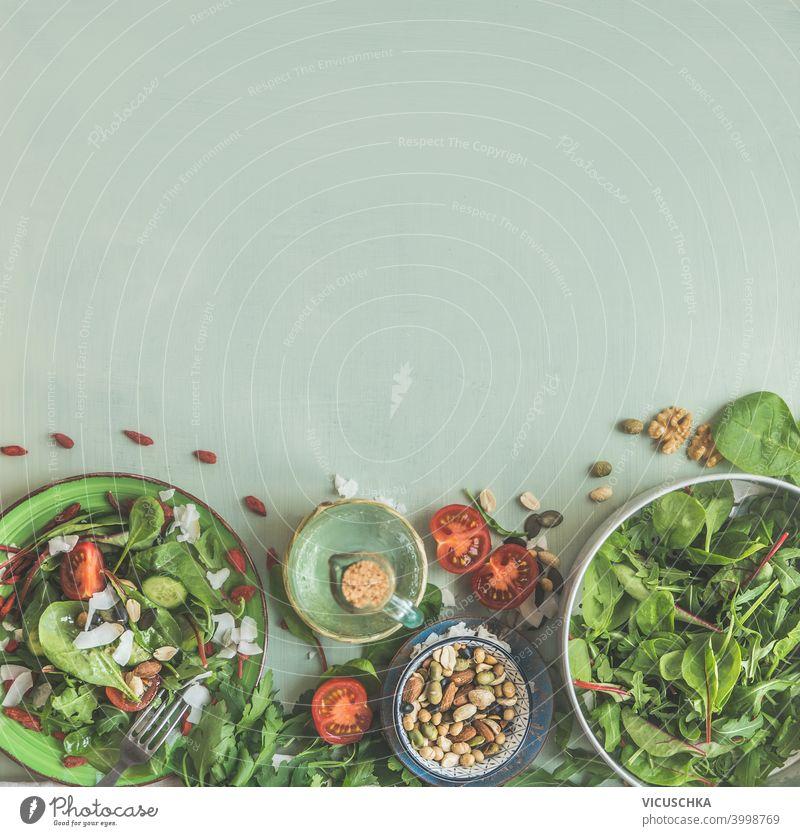 Grüner Salat mit Nüssen in Platten auf hellgrünem Hintergrund mit Zutaten. Gesundes Mittagessen. Ansicht von oben. Rahmen. Kopierraum Salatbeilage Muttern Belag