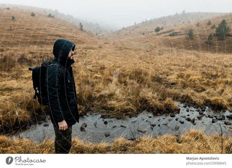 Junger Mann erkundet die Natur an einem nassen Wintermorgen in den Bergen Abenteuer allein Herbst Rucksack Backpacker Herausforderung kalt Erkundung erkunden