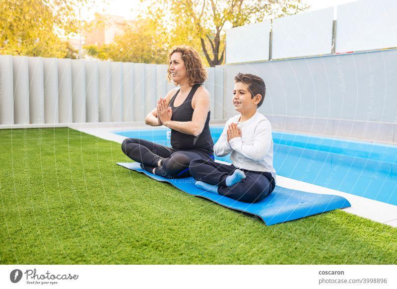 Mutter und Sohn machen Yoga-Übungen in ihrem Hausgarten Aktivität Asien Körper Windstille Kind Kindheit niedlich Familie Familien-Yoga Frau passen Garten
