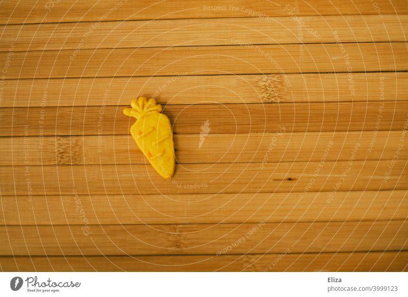 Gelb orangener Karottenkeks auf Holz Keks gelb lecker Ostern Linien liniert