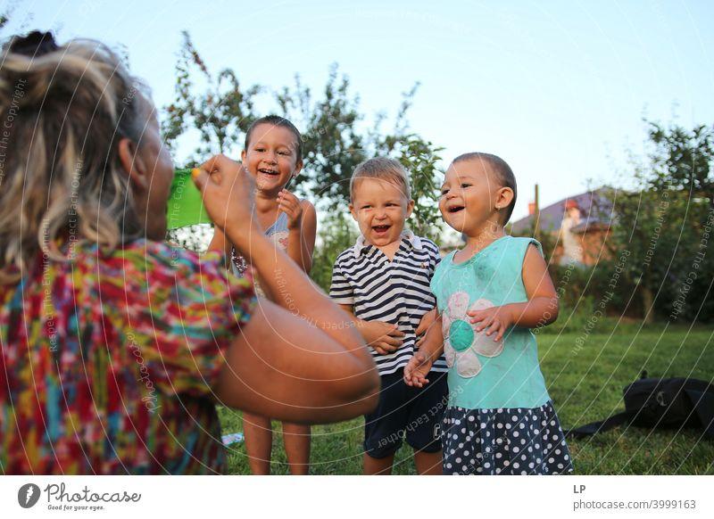 """drei Kinder, die sich amüsieren, über einen Erwachsenen lachen, sich lustig machen Spaßfaktor lustige Action lustig,"""" Freude Aktion Glück Spielen Spaß haben"""