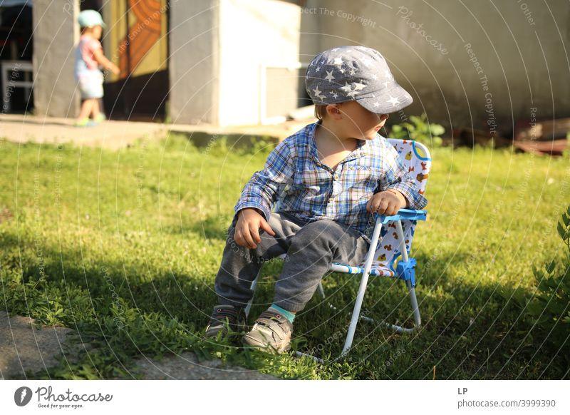glückliches Kind, das sich ausruht und sich auf einen Stuhl setzt und wegschaut Erholung Mitteilung Körpersprache amüsant Entertainment Kindheitserinnerung