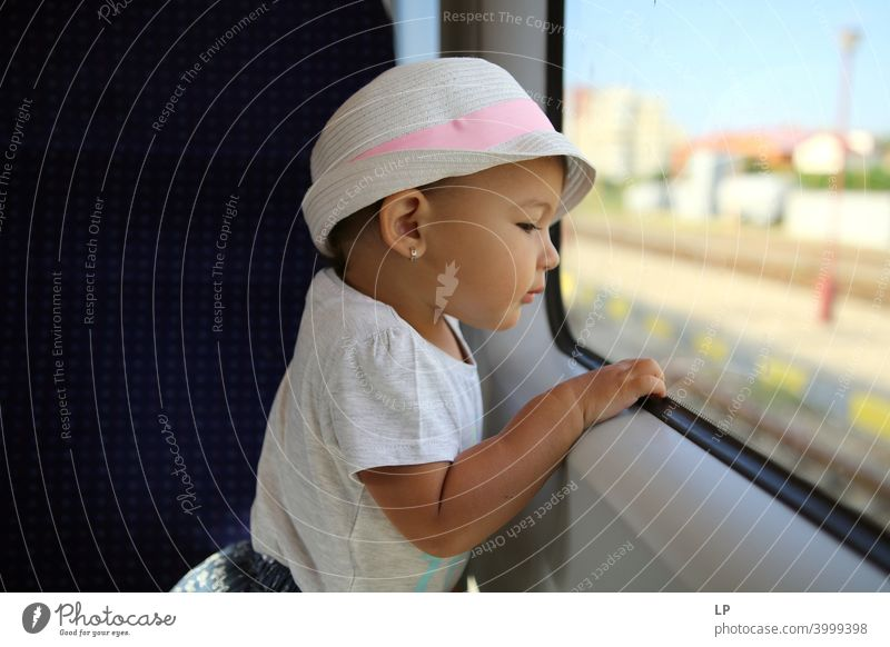 kleines Mädchen mit Hut, das aus einem Zugfenster schaut Wegsehen Oberkörper Kontrast Licht Textfreiraum unten Strukturen & Formen Muster abstrakt