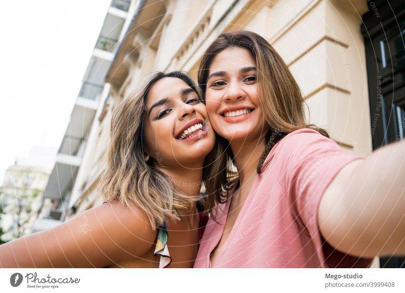 Zwei Freunde machen ein Selfie im Freien. jung zwei Frau Großstadt Freundschaft Lachen Porträt Spaß Tourismus reisen Genuss Lächeln Blick niedlich Freizeit