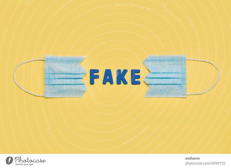 """Zweigeteilte chirurgische Schutzmaske mit Buchstaben, die das Wort """"Fake"""" bilden - Konzept des Protests gegen Coronavirus-Betrug Chirurgische Schutzmaske"""