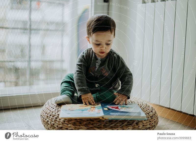 Kleinkind liest ein Buch zu Hause Kind Kindheit 0-12 Monate 1-3 Jahre Kaukasier lesen Bildung lehrreich Freude Glück niedlich Lifestyle Mensch Baby Tag Farbfoto