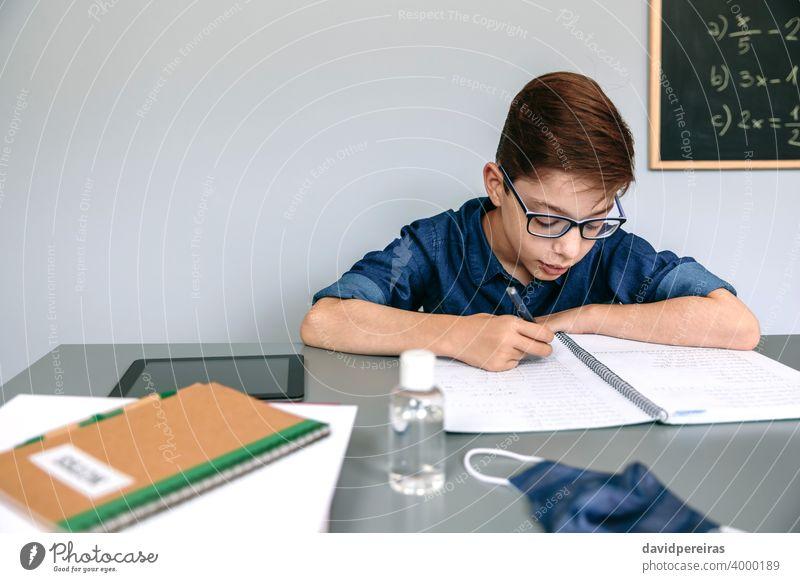 Junge schreibt in der Schule in sein Notizbuch Klassenraum Maske auf dem Schreibtisch Handdesinfektionsmittel Coronavirus Sicherheit schreibend Virus Menschen