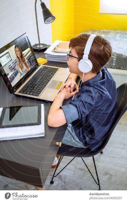 Preteen mit Kopfhörer erhalten Klasse zu Hause mit Laptop aus seinem Schlafzimmer Kind abgelegene Schule Schule zu Hause Lehrer Videoanruf hören Jugendzimmer