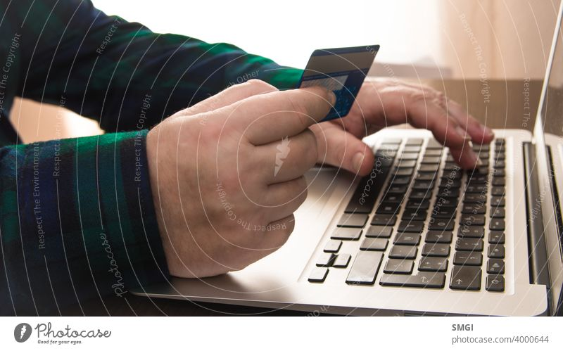 Nahaufnahme von einer Hand, die eine Kreditkarte vor einem Laptop hält. Konzept der Kartenzahlung im Internet. Erwachsener Banking Rechnung kaufen Postkarte
