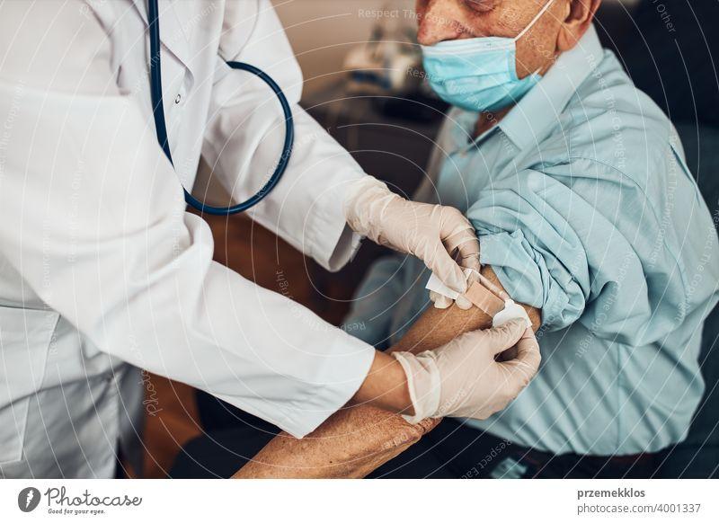 Arzt setzt ein Pflaster anstelle der Impfstoffinjektion bei einem älteren männlichen Patienten. Impfung gegen Covid-19 oder Coronavirus geduldig Person