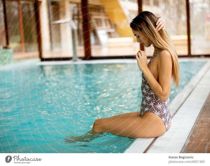 Schöne junge Frau sitzt am Schwimmbad Erwachsener attraktiv schön Schönheit blau Körper Kaukasier niedlich Tag Fitness im Innenbereich Freizeit Lifestyle Model