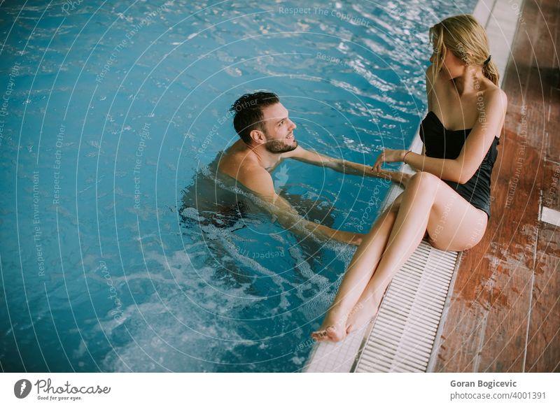 Junges Paar entspannt sich am Rande des Innenpools 20s Erwachsener attraktiv schön Schönheit Bikini Kaukasier heiter niedlich Saum genießen genießend Genuss