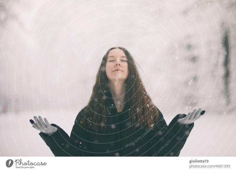 Junge Frau, Teenager meditiert draussen bei Schneefall im Winter Tag amazing Jahreszeiten Textfreiraum oben Winterwald Park Natur Januar kalt draußen feminin