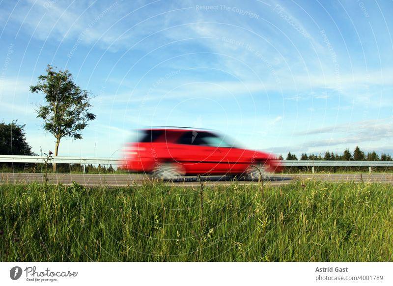 Schnelles Fahren auf deutschen Straßen. Ein rotes Auto rast eine Straße entlang auto fahren autofahren straße rasen raser schnell schnelles rasant deutschland