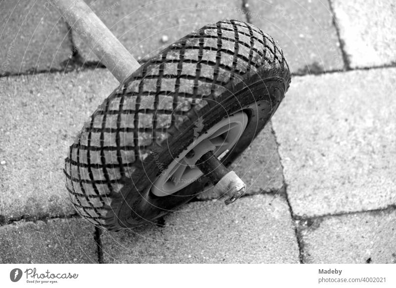 Rad einer alten Sackkarre an einem selbsgebauten Dreirad auf einem Bauernhof in Rudersau bei Rottenbuch im Kreis Weilheim-Schongau in Oberbayern, fotografiert in klassischem Schwarzweiß