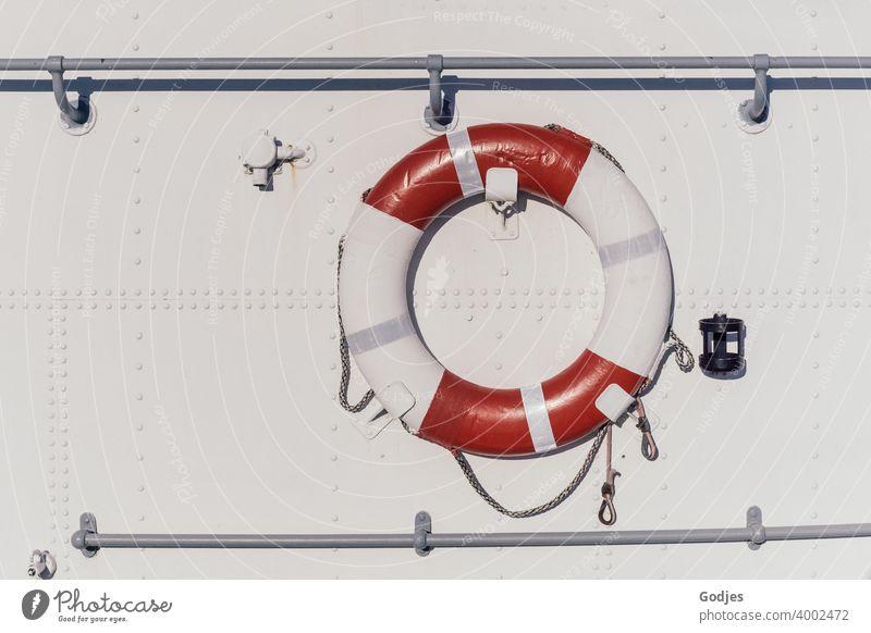 Rettungsring an metallener weißer Schiffswand Schifffahrt Farbfoto Außenaufnahme Menschenleer Sicherheit Wasser Meer Tag Wasserfahrzeug rot Bootsfahrt blau