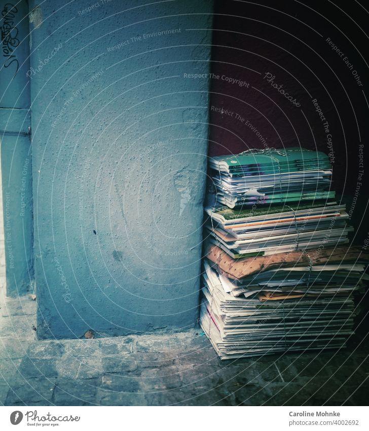 Zeitungsstapel gebündelt an einer Hausmauer Altpapier Papier Stapel Recycling Farbfoto Medien Printmedien Zeitschrift Information Bildung lesen Journalismus
