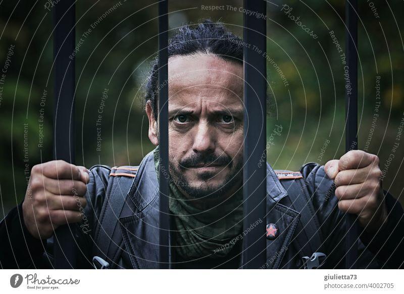 Porträt eines wütenden Mannes mit zornigem Blick und geballten Fäusten hinter Gitterzaun Gewalt maskulin brutal Bart Blick in die Kamera Eisentor Kriminalität