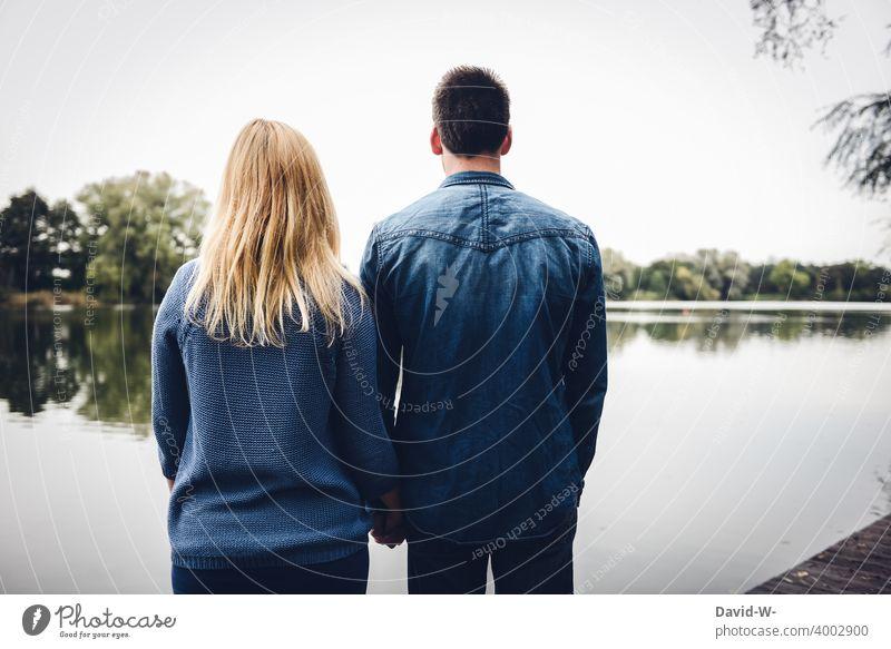 Mann und Frau stehen gemeinsam am See und blicken in die Ferne zusammen Pärchen Liebe zusammenhalt Blicken Natur Zusammenhalt Gemeinschaft Rückansicht