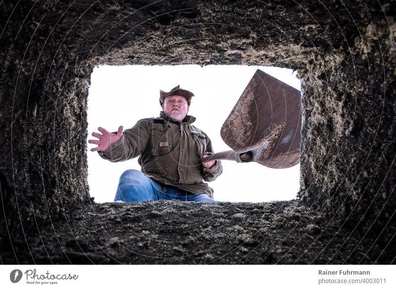 Ein Mann mit einer Schaufel steht an einem offenen Grab. Er blickt entsetzt in die Tiefe. Beerdigung beerdigen Seuche Pandemie Covid-19 Virus Infektionsgefahr