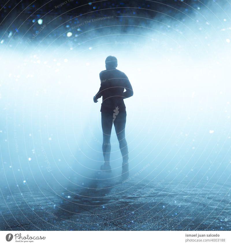 Mann läuft auf der Straße in nebligen Tagen in der Wintersaison eine Person rennen laufen Marathon Läufer Joggen Aktion Fitness Gesundheit Lifestyle Jogger