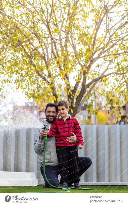 Vater und Sohn bewässern das Gras auf ihrem Haus aktiv Aktivität Baby Hinterhof Junge Kind Kindheit Papa Tropfen Familie Spaß Spiel Garten Gartenarbeit Glück