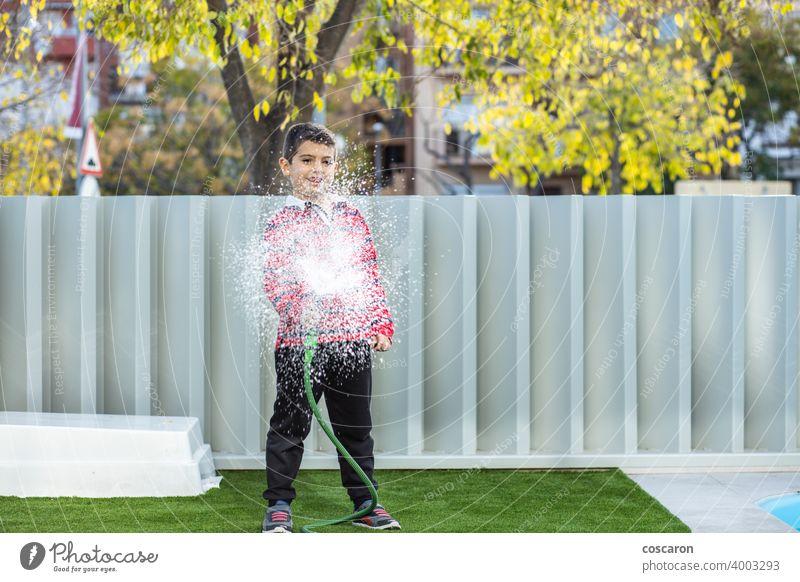 Kleiner Junge bewässert das Gras im Garten Aktion Aktivität Kind Kindheit Kinder Tropfen genießen Familie Springbrunnen frisch Spaß Gartenarbeit grün