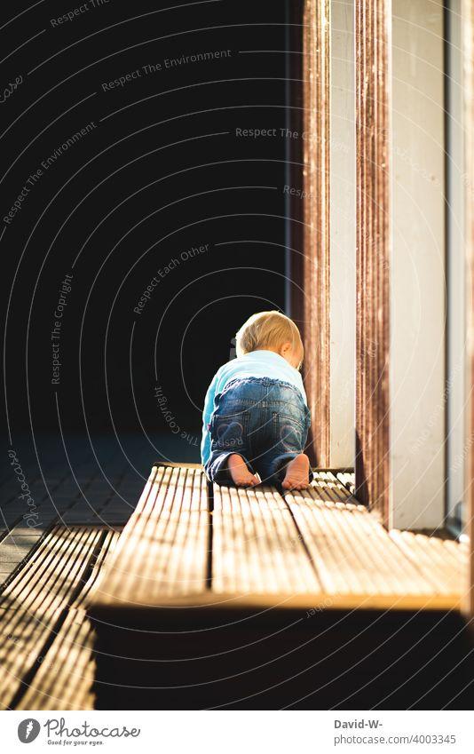 krabbelndes Kind auf dem Weg in den Garten draußen erkunden interessiet Sonnenschein Sonnenlicht Sommer Frühling Barfuß niedlich Kindheit entdecken