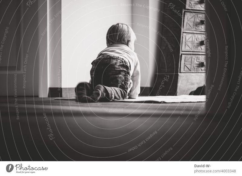 Kleinkind zu Hause krabelt über den Fußboden und blickt nach draußen Kind nachdenklich psyche Corona Gedanken kontaktverbot denken einsam alleine Quarantäne