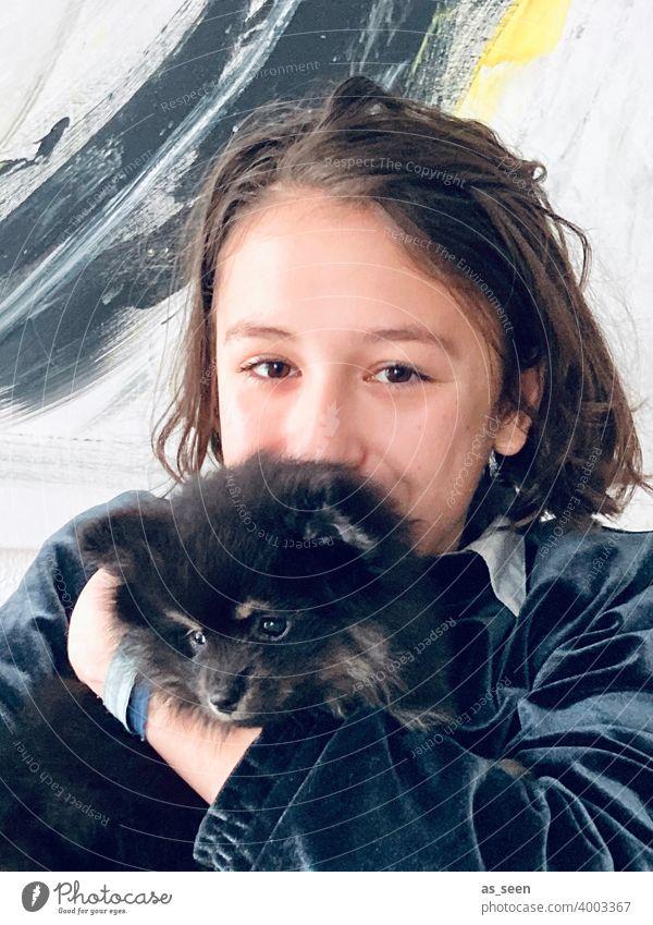 Mädchen trägt Black Pomeranian Welpen Zwergspitz Hunderasse Blick in die Kamera Freude Tierliebe Farbfoto 1 Haustier Tag niedlich Freundlichkeit Tiergesicht