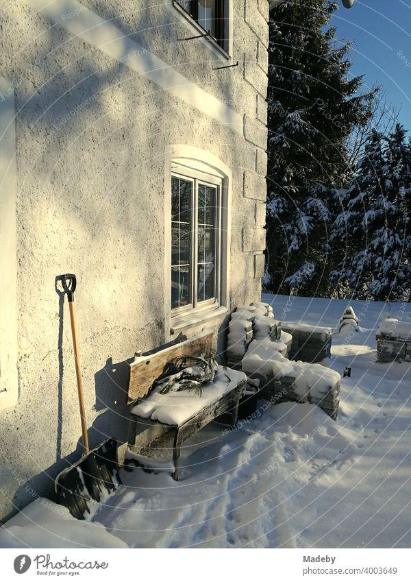 Verschneite Holzbank und angelehnte Schneeschaufel an einem alten Bauernhaus im Winter bei Sonnenschein in romantischer Schneelandschaft in Rudersau bei Rottenbuch im Kreis Weilheim-Schongau in Oberbayern