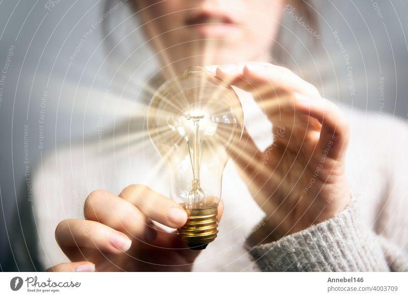 Weibliche Hand hält eine leuchtende Glühbirne, große Idee, Innovation und Inspiration, Business-Konzept Hintergrund Licht Knolle Energie Lampe hell Elektrizität