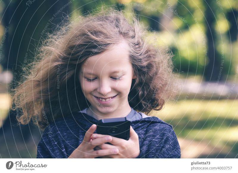 Porträt eines glücklichen Jungen mit langen Haaren beim Lesen von lustigen Nachrichten auf seinem Handy Vorderansicht Oberkörper Zentralperspektive