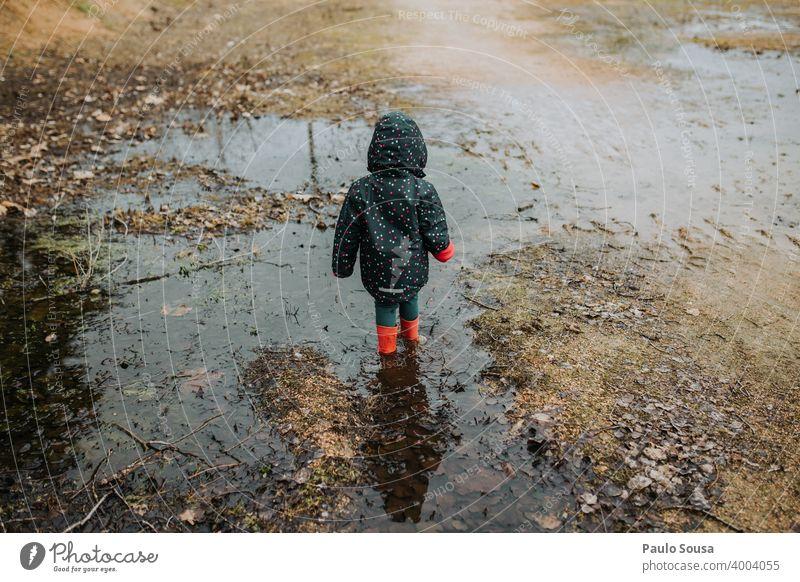 Kind mit roten Gummistiefeln spielt auf einer Pfütze Kindheit Mädchen Wasser Mensch Stiefel Spielen Regen dreckig Tag Textfreiraum unten Kleinkind