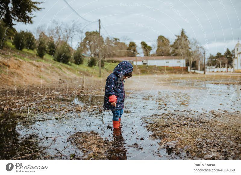 Kind mit roten Gummistiefeln spielt auf einer Pfütze Kindheit Regen authentisch Mensch Spielen Wasser nass Außenaufnahme Freude Farbfoto Stiefel Fröhlichkeit