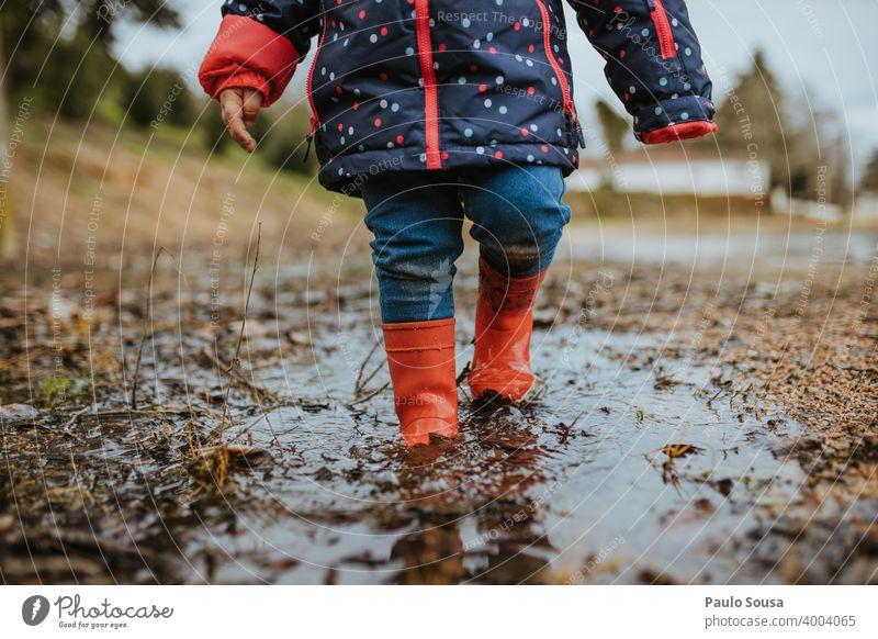 Kind mit roten Gummistiefeln spielt auf einer Pfütze Kindheit Außenaufnahme Wasser Spielen Wetter schlechtes Wetter dreckig Stiefel Farbfoto Tag Freude Herbst
