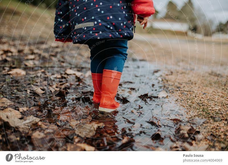 Niedriger Ausschnitt Kind mit roten Gummistiefeln geht auf Pfütze Kindheit authentisch Spielen Außenaufnahme Herbst dreckig Tag Wasser nass Mensch Freude