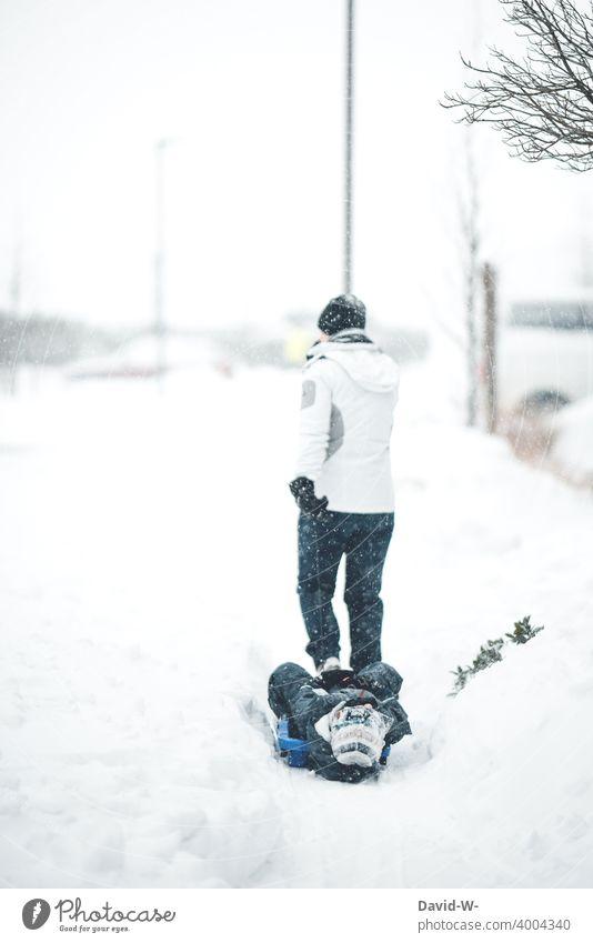 Mutter zieht Kind mit dem Schlitten durch den Schnee ziehen Winter Wintertag winterlich weiß Winterstimmung kalt draußen Wintereinbruch