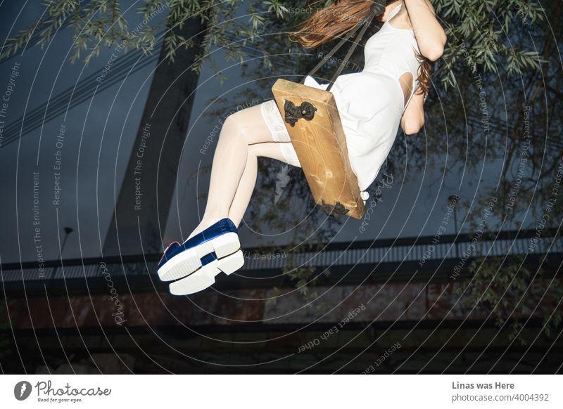 Eine Frau in weißem Outfit mit ihren extrem langen Beinen schwingt unter der Brücke. Der Himmel ist dunkelblau, und die Stimmung ist gut. Ihre modischen blauen Schuhe leuchten schon von weitem.