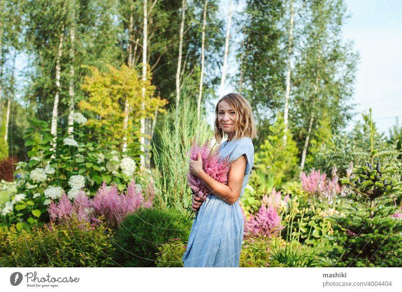 Frau Gärtnerin posiert mit Strauß Astilbe Blumen in privaten Garten. Landleben und Landschaftsgestaltung Konzept Gartenarbeit Pflanze Glück Kaukasier Lifestyle